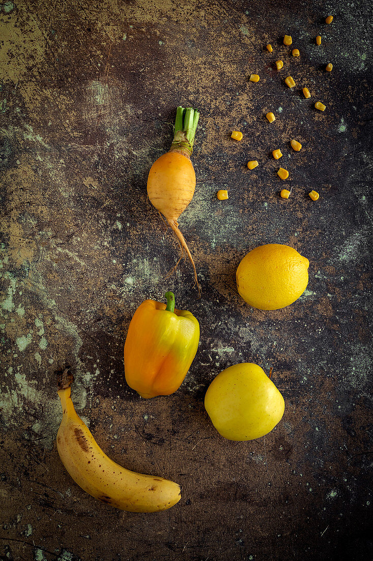 Mix of fruits and vegetables in yellow color on rusty background