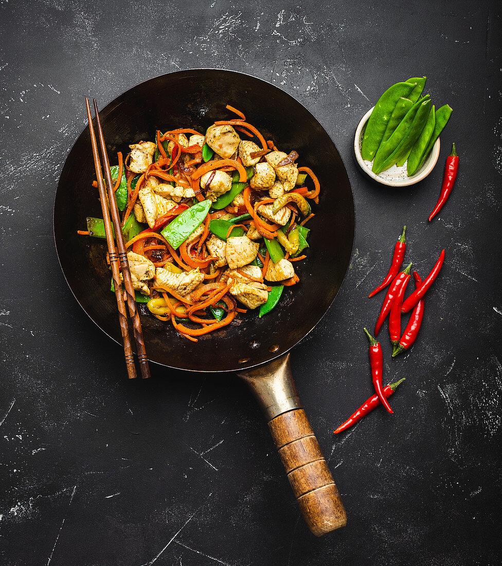 Stir fry chicken with vegetables in old rustic wok pan