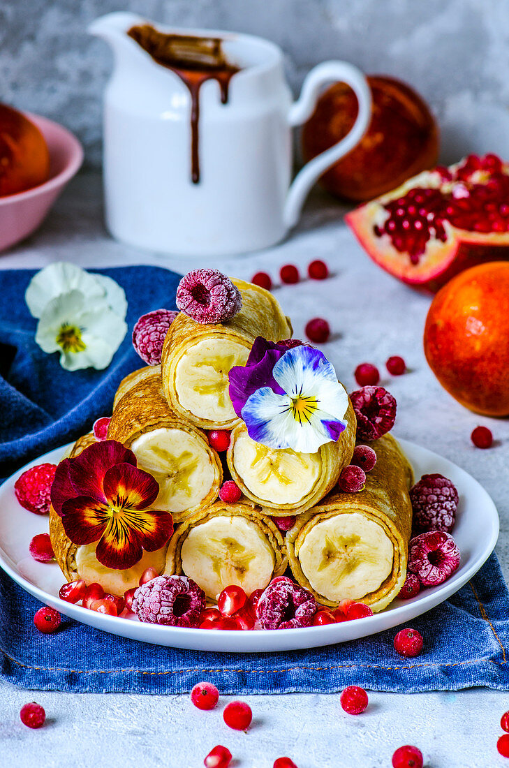 Thin pancakes with whole bananas, frozen berries and edible violets