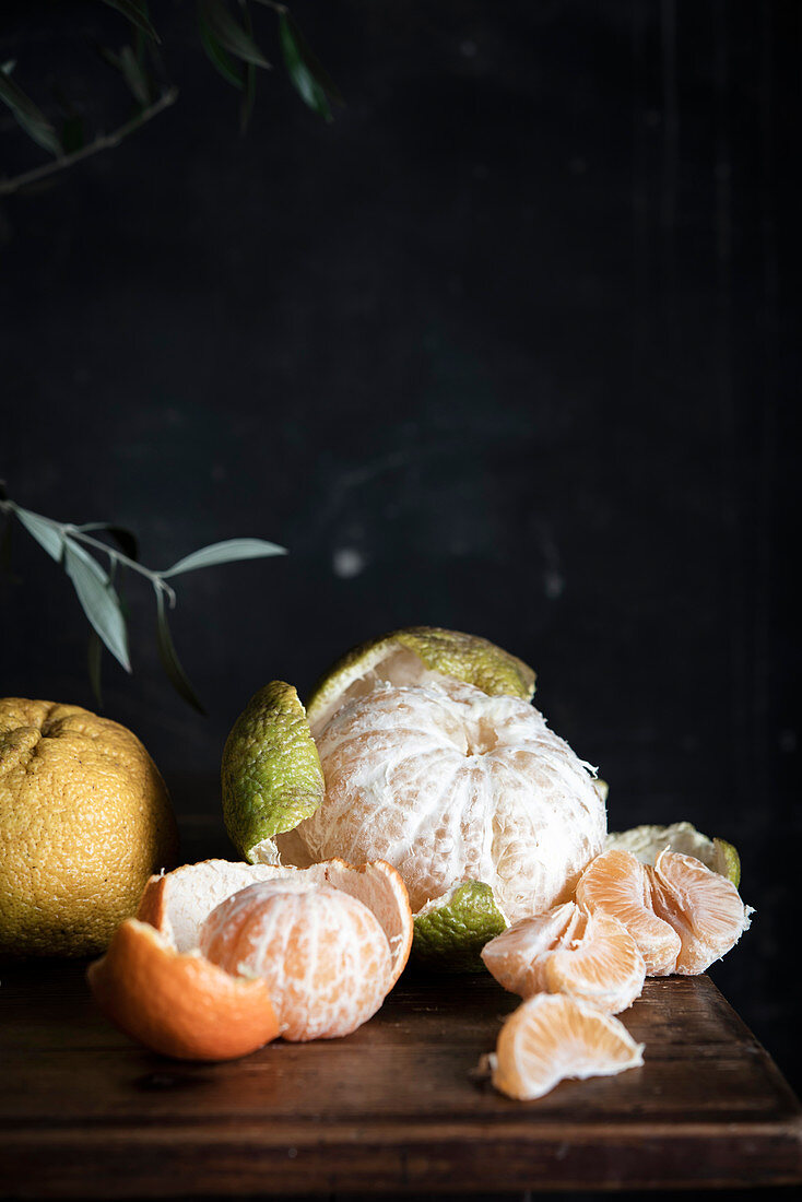 Various citrus fruits, partially peeled