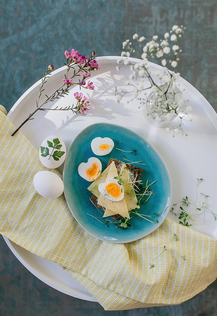 An open sandwich with cheese, a boiled egg and cress