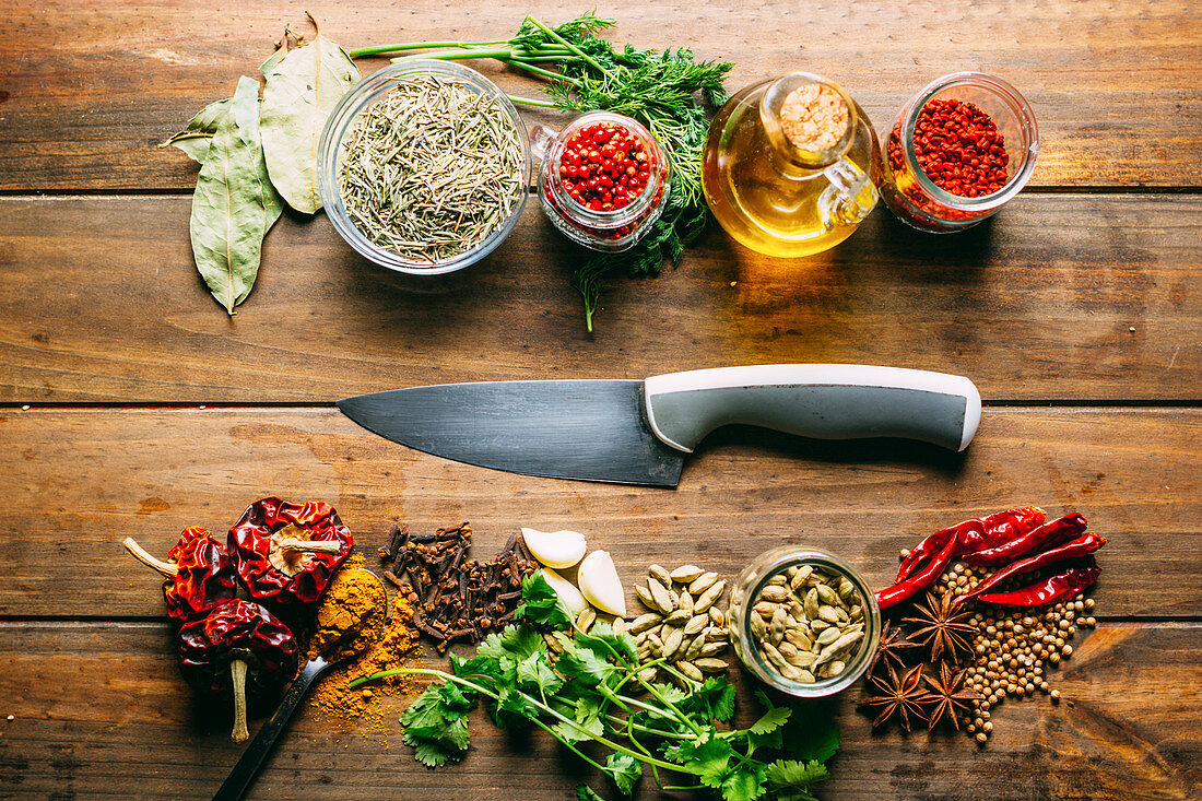 Verschiedene Gewürze, Kräuter, Knoblauch, Chilischoten und Olivenöl