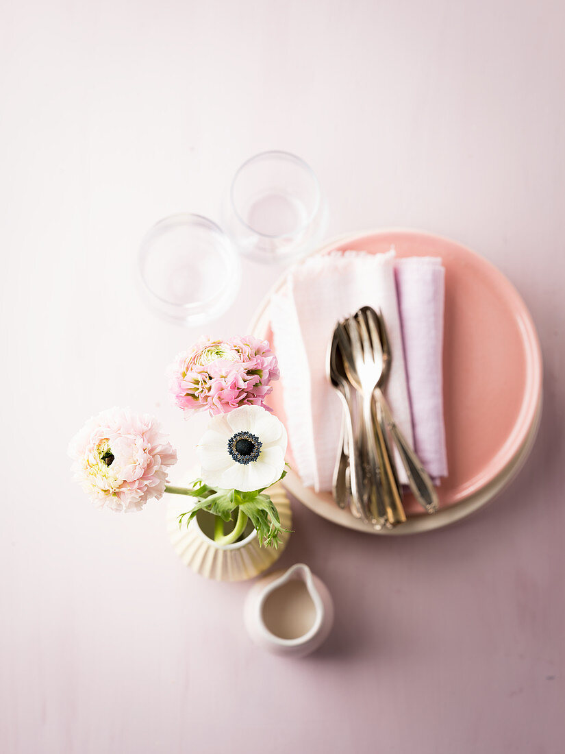 Napkins and cutlery on stacked plates with glasses and vase of flowers