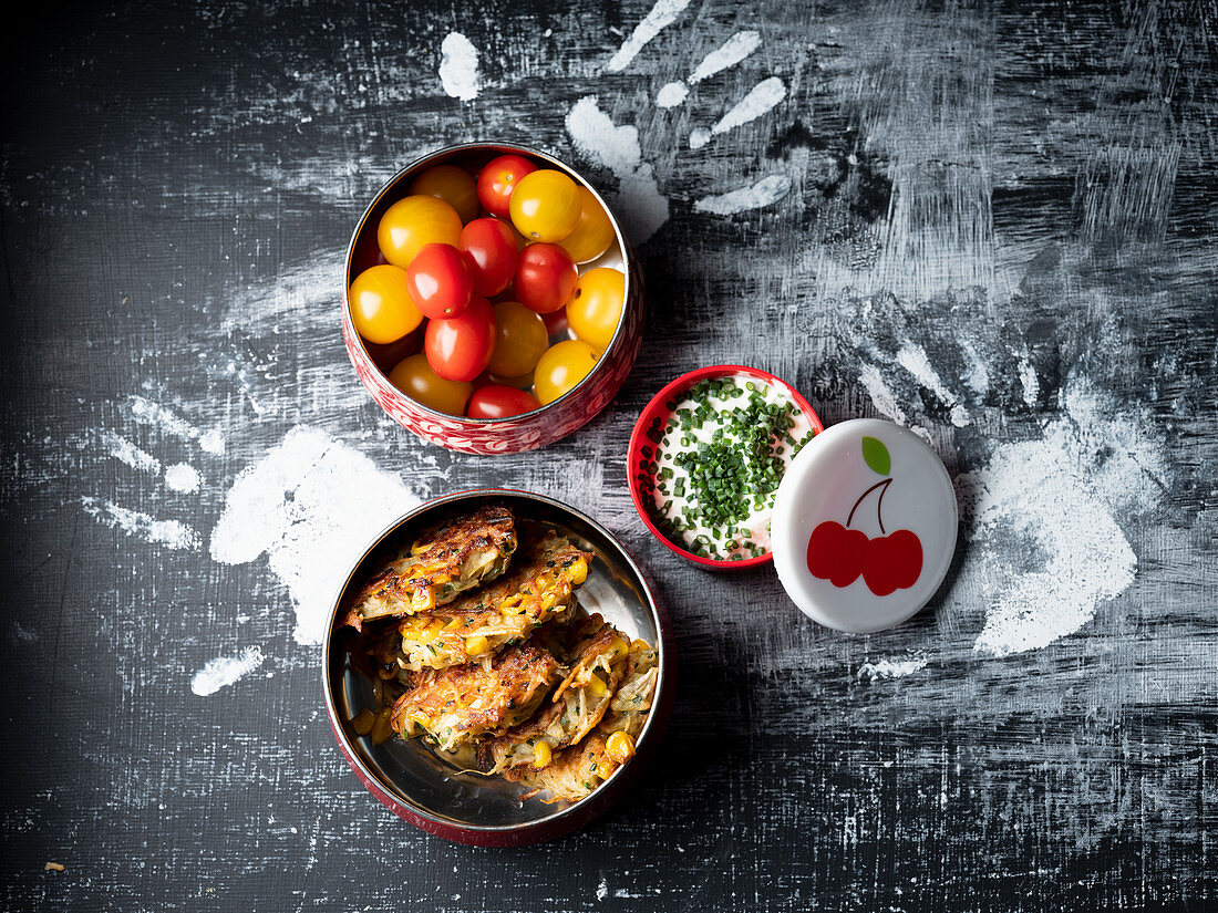 Vegetable fritters, herb cream cheese and tomatoes in a tin