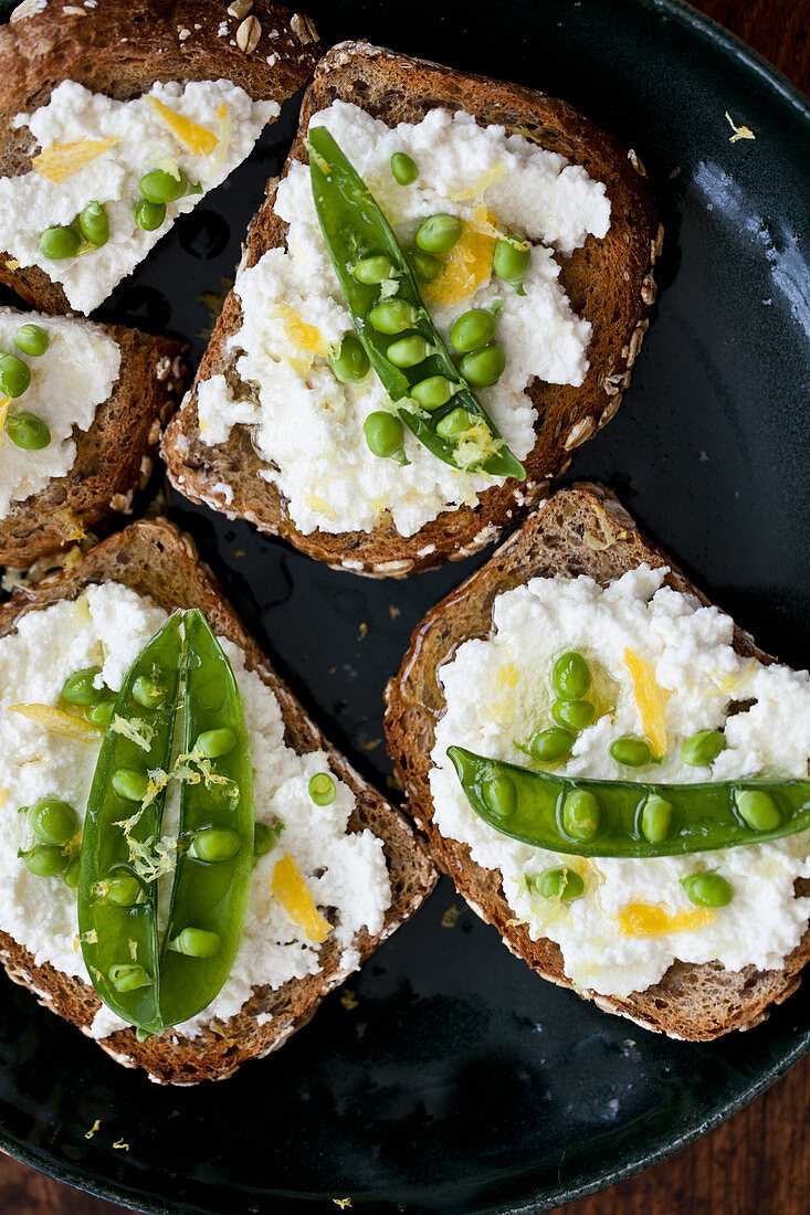 Whole wheat toast topped with ricotta, peas, lemon zest and olive oil