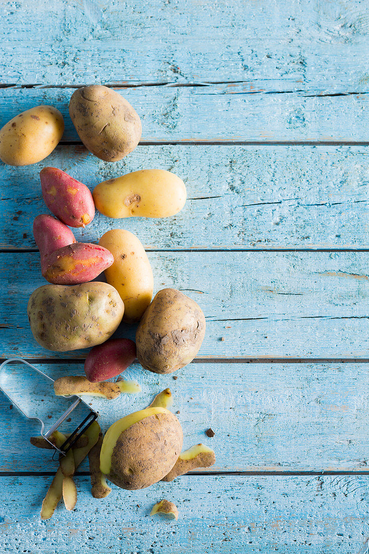 Various potatoes on a pale blue wooden background