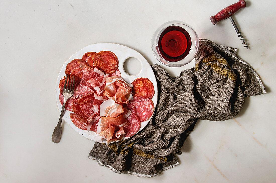 Antipasto meat platter assorti of sliced jamon, salami, chorizo sausage on white ceramic board with glass of red wine