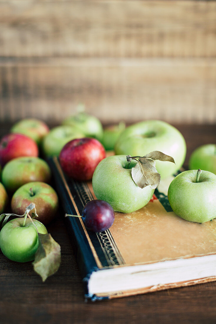 Bunch of ripe apples and small plum lying on shabby old book