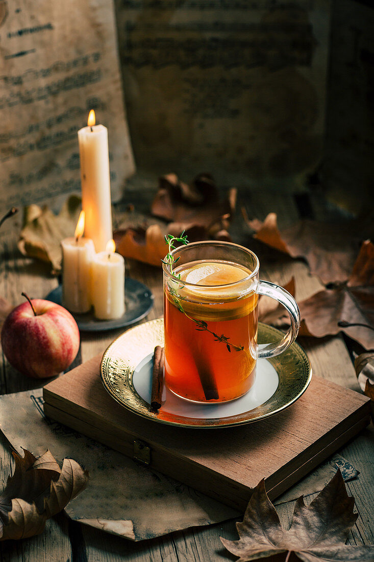 Cup of fresh tea with lemon, ripe apple and flaming candles amidst autumn leaves