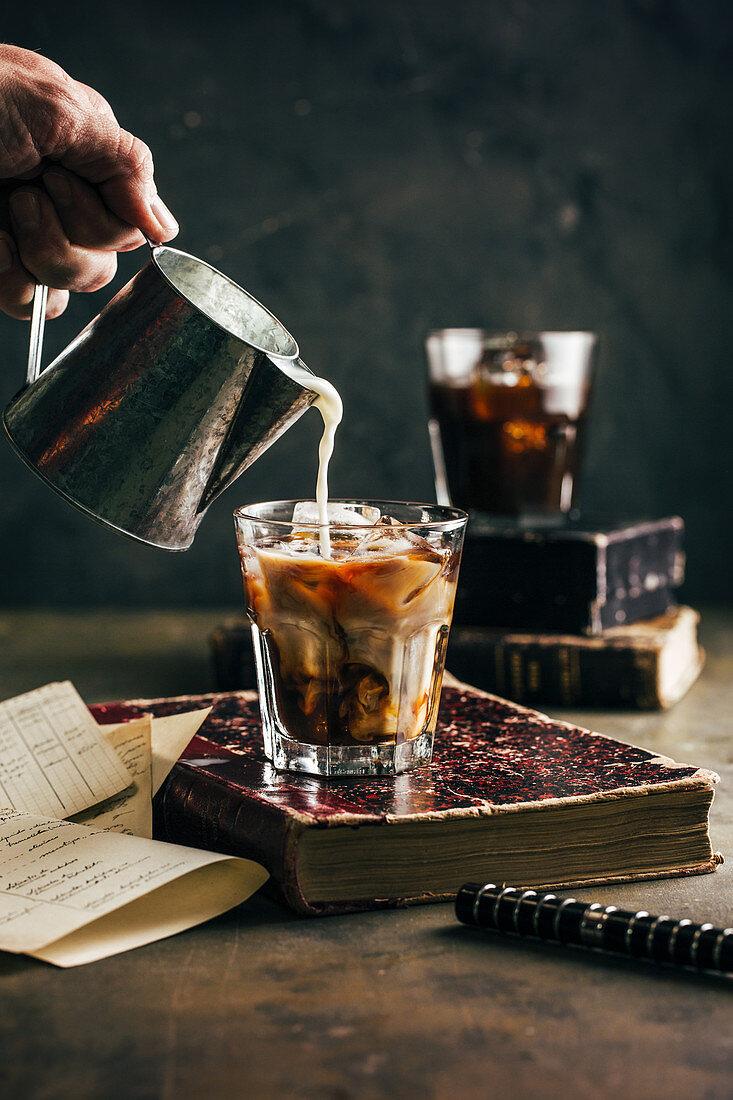 Pouring milk in a cold espresso coffee glass