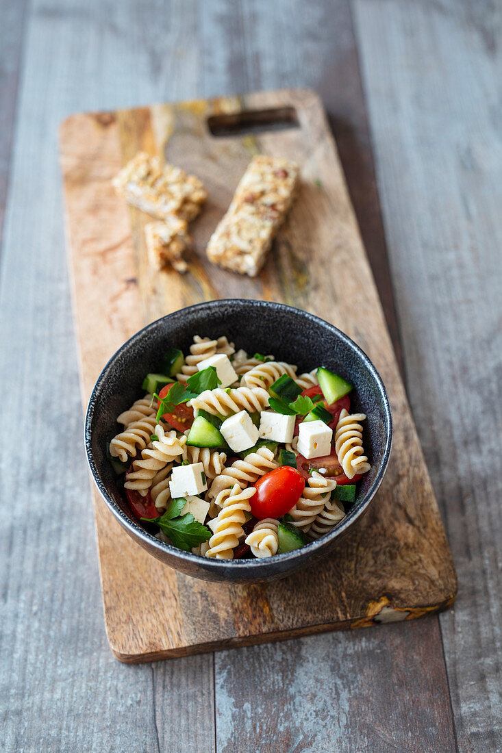 Wholegrain pasta salad with tomato, feta and cucumber, served with cereal bars