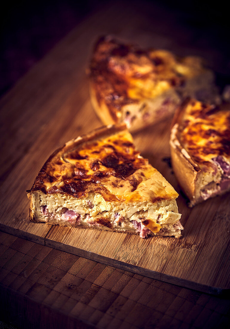 Three pieces of bacon quiche on a wooden board