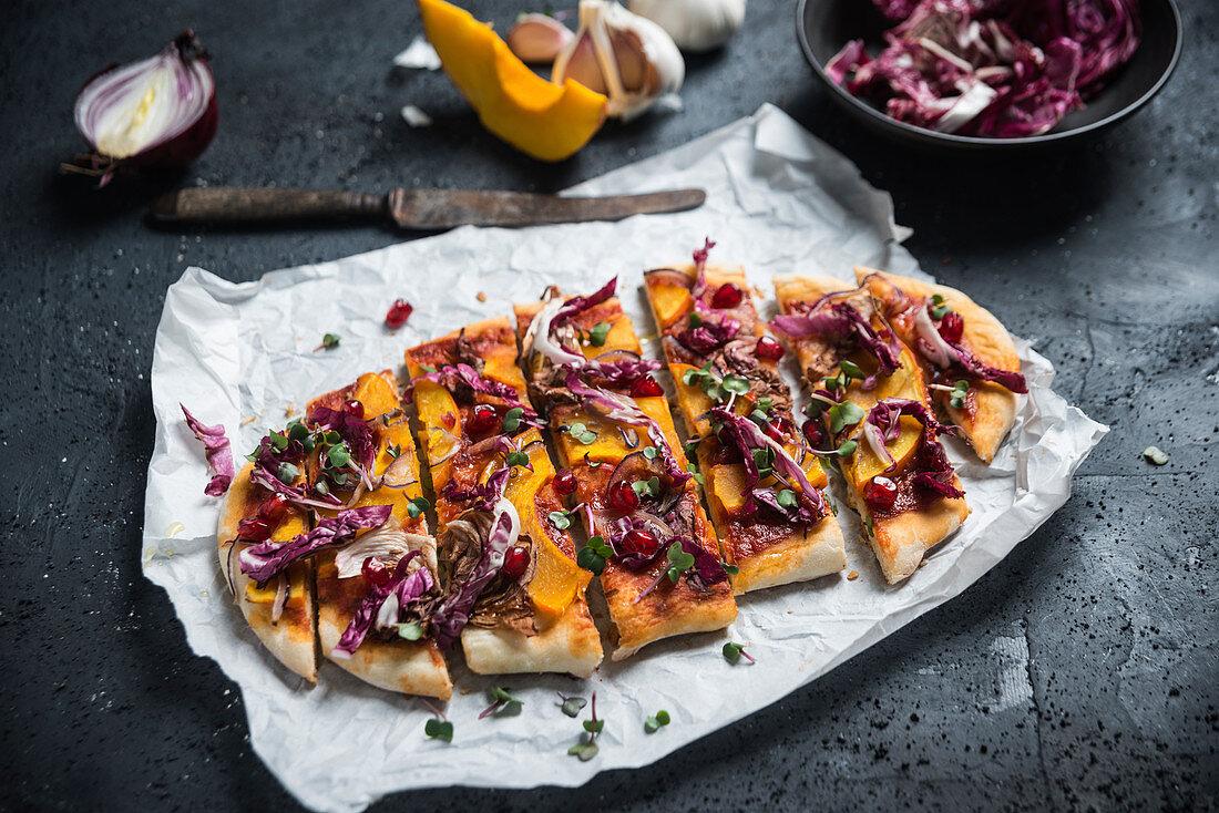 Vegan spelt pizza with pumpkin, radicchio, red onion, pomegranate and radish cress