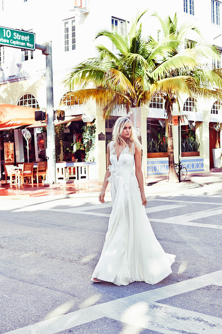Junge blonde Frau in einem weißen Brautkleid auf der Straße