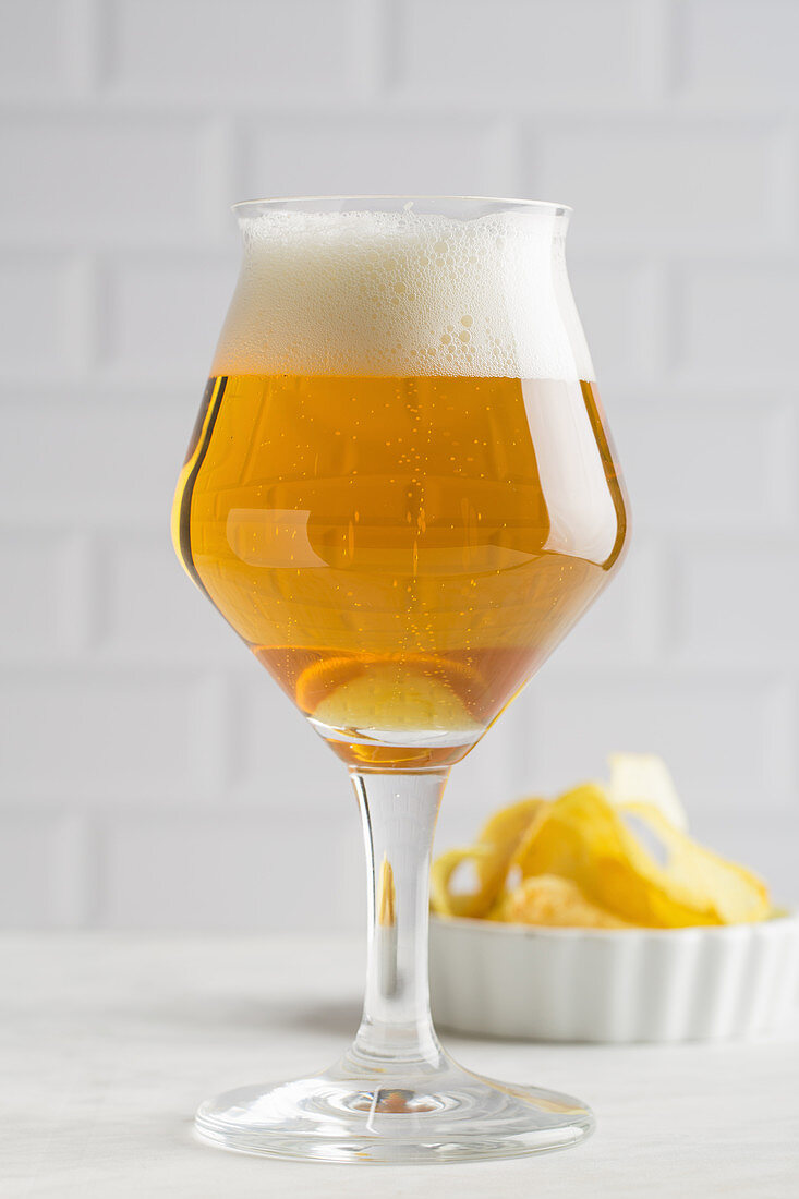Glass of beer and chips on light background