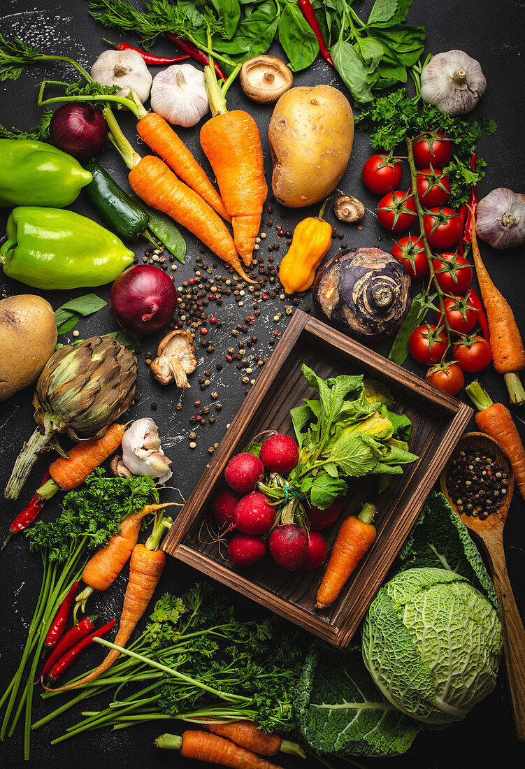 Radish and carrot fresh bunch in old wooden box and fresh farm organic vegetables on rustic black concrete background