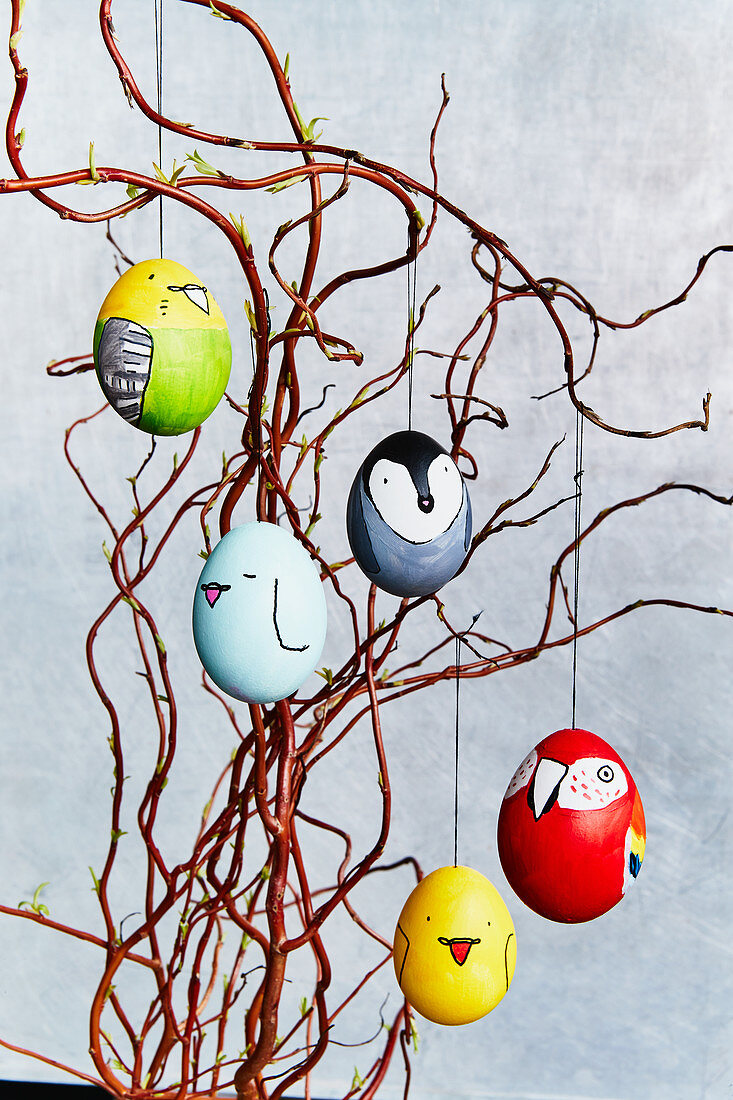 Easter eggs decorated with bird motifs hung from twigs