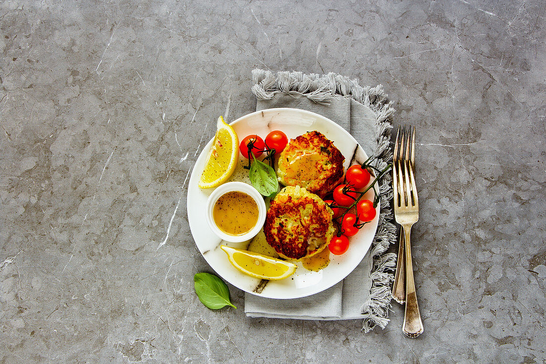 Vegetarian cauliflower cakes with dip and vegetables