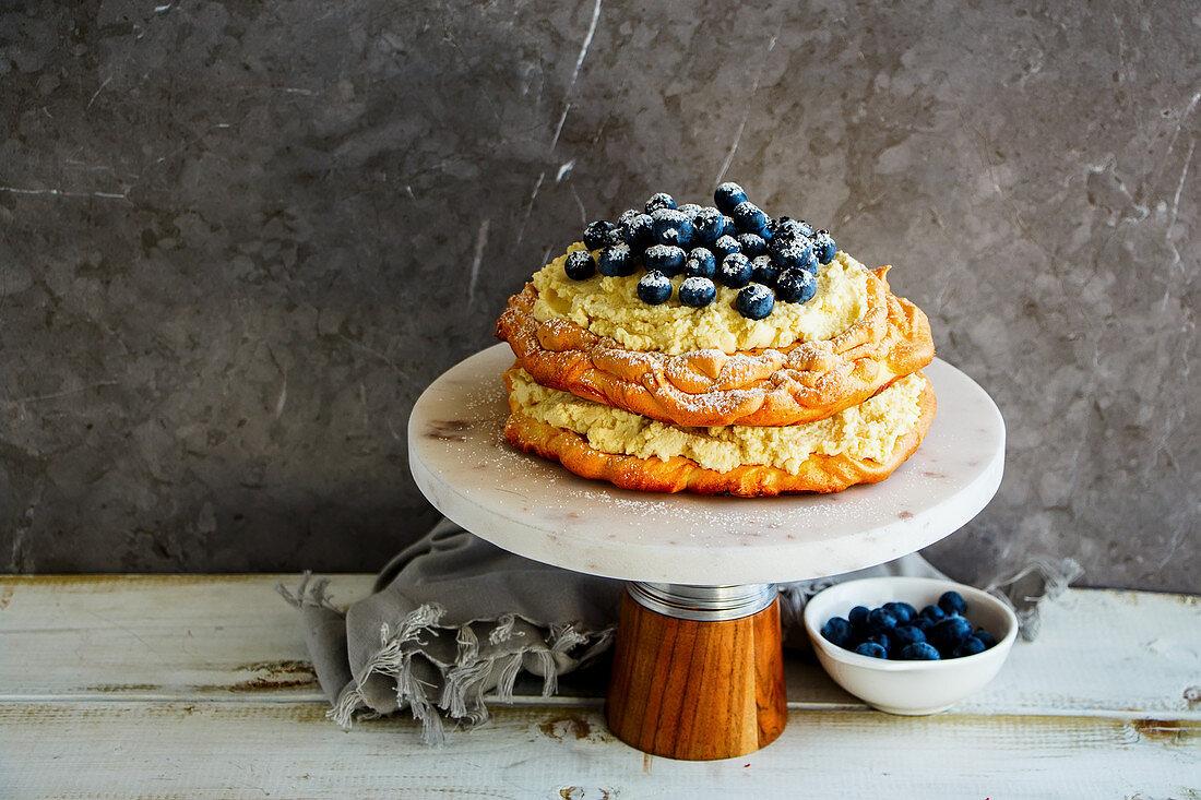 Meringue Pavlova cake on cake stand with blueberry and mascarpone cream