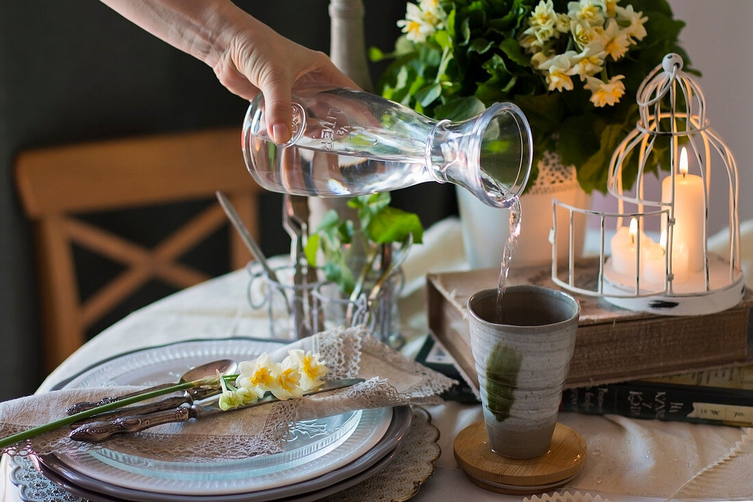 Spring table settings in green colors with Daffodils, female hand pouring water