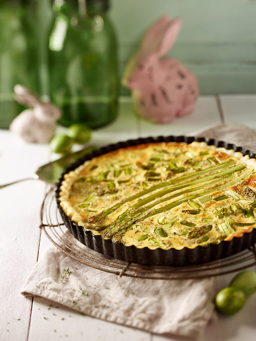 Green asparagus tart on a wire rack with Easter decorations