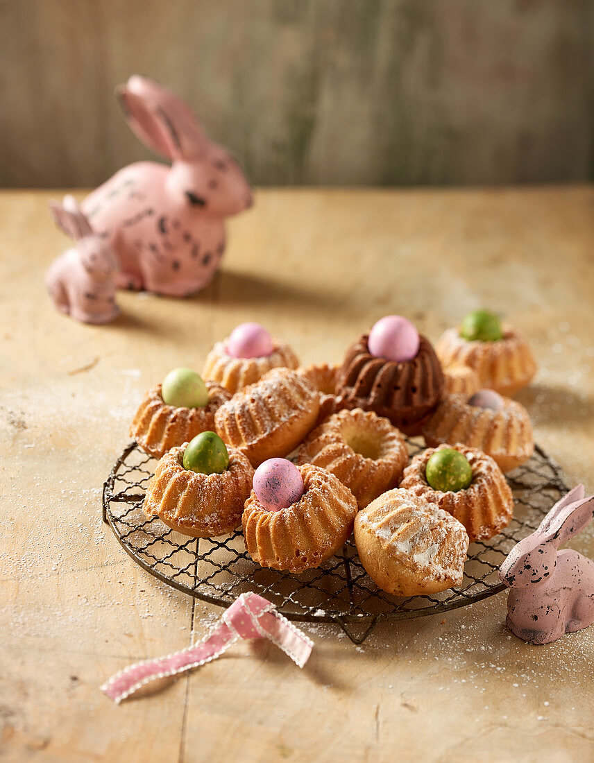 Mini Bundt cakes on a wire rack with dyed quail's eggs and Easter decorations