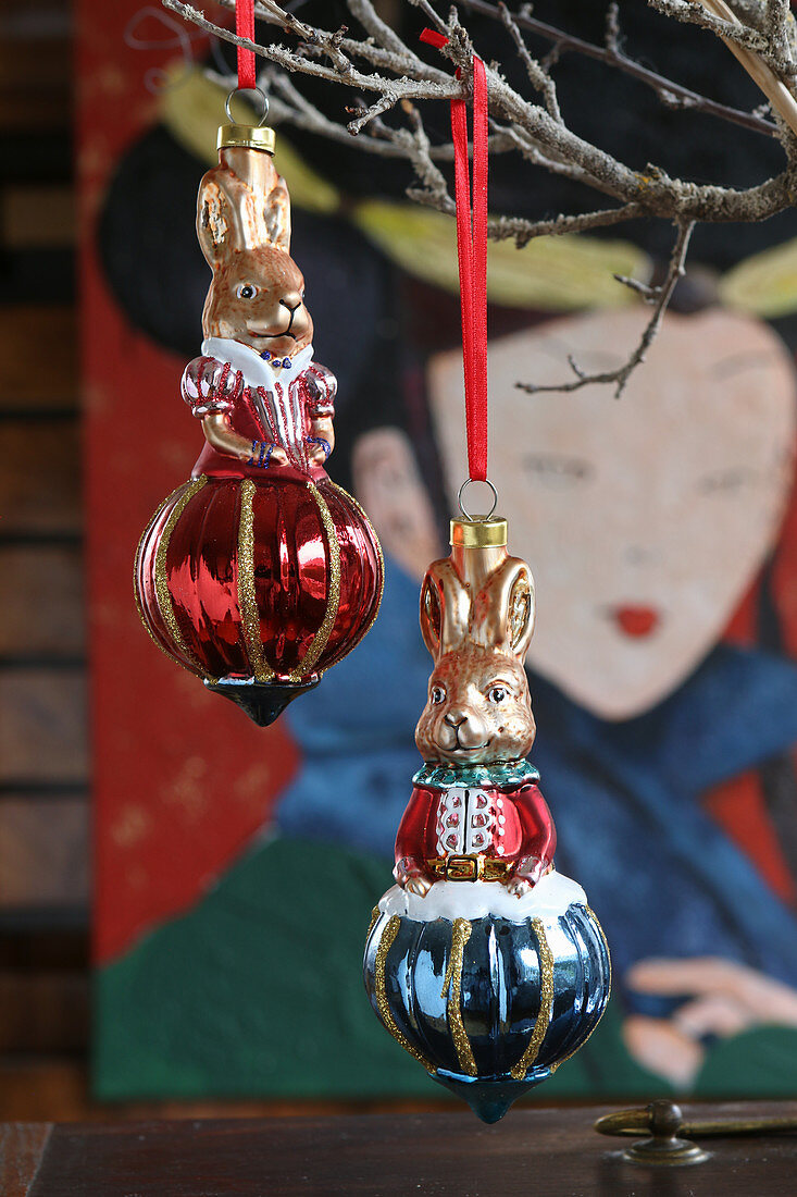 Red and blue rabbit-shaped Christmas-tree baubles hung from twigs