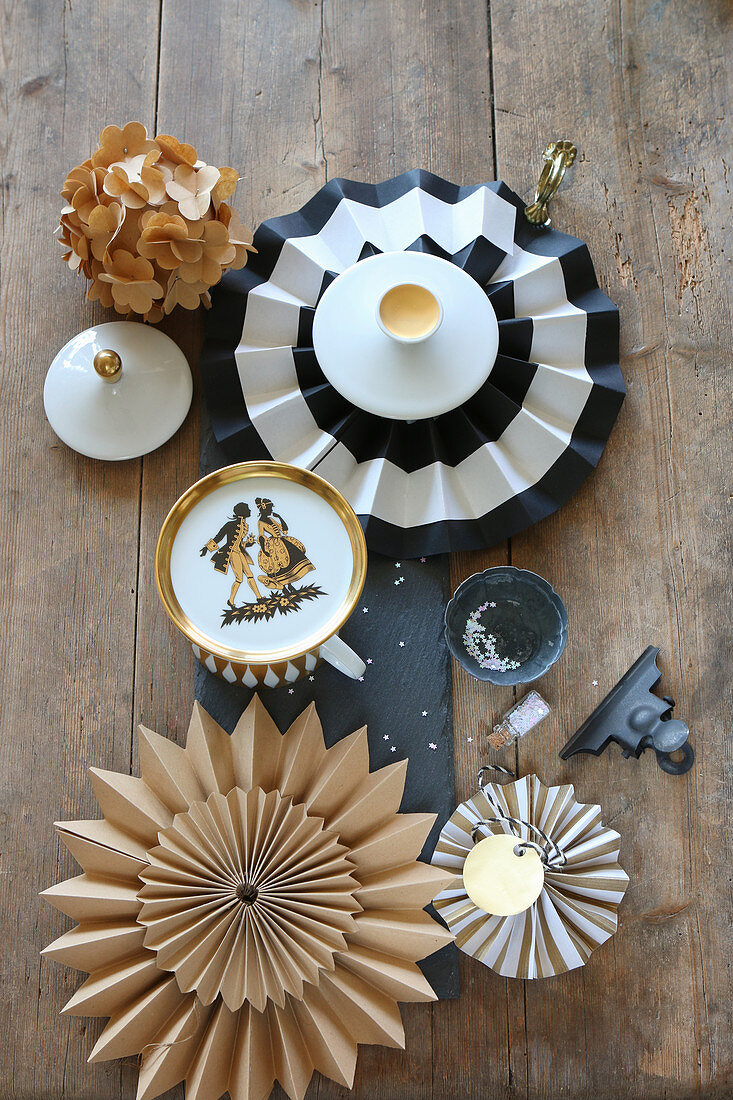 Festive arrangement of vintage plate, paper flowers, star and grey candles on slate board decorating table