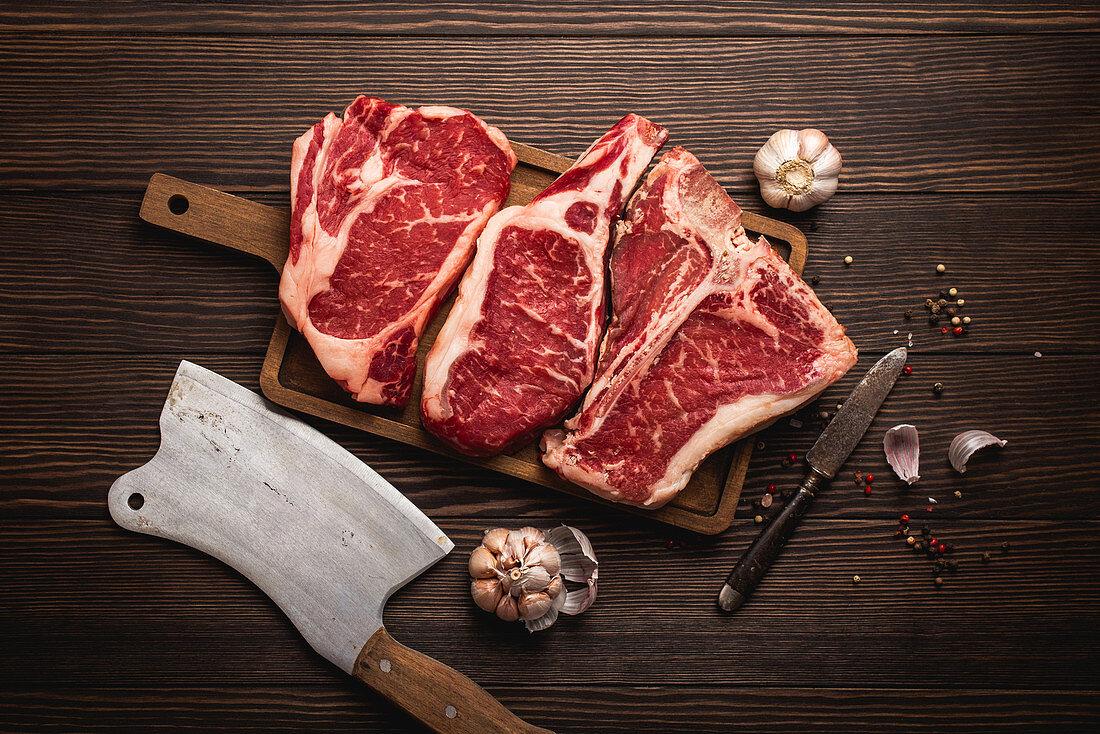 Raw rib-eye steak, a T-bone steak and a cowboy steak