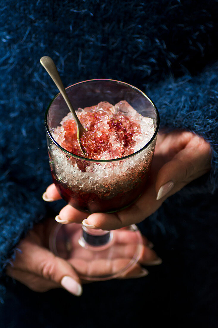 A woman holding a glass of crushed ice with raspberry syrup