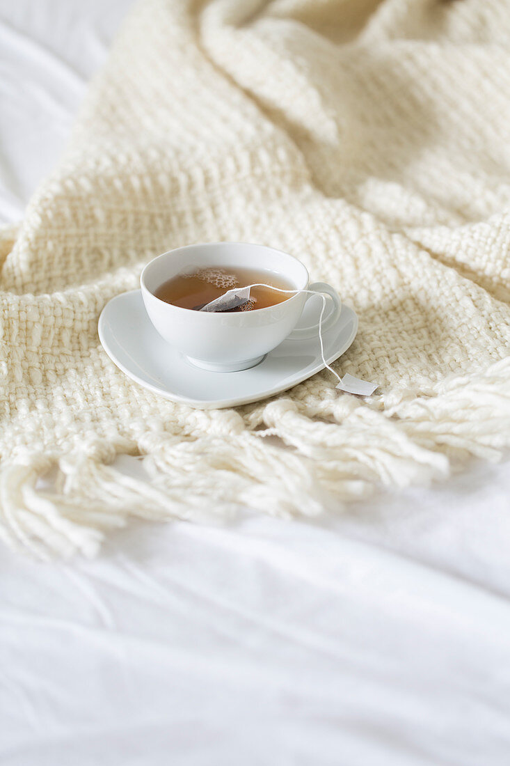 A cup of tea with teabag on a woollen blanket on a bed