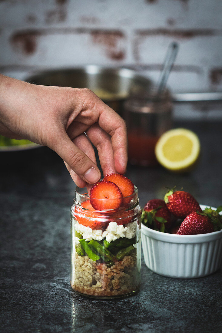 Bulgur salad with green asparagus, feta cheese and strawberries in a jar