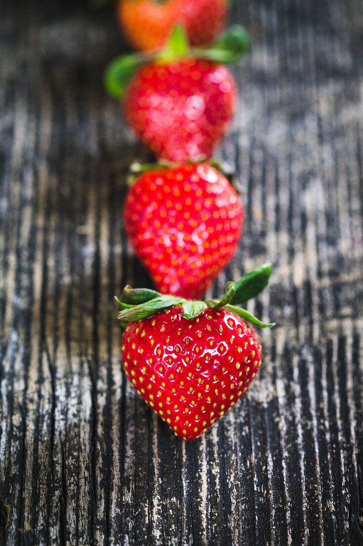 A row of strawberries on a wooden surface