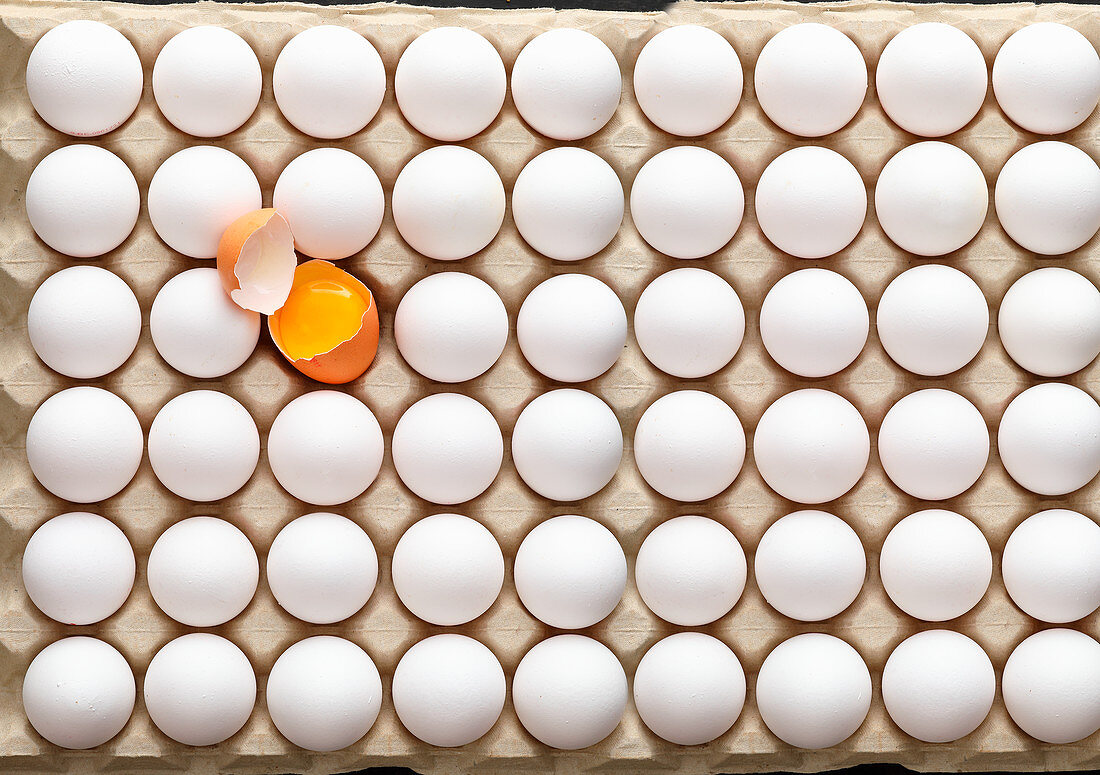 A palette of white eggs, one cracked open