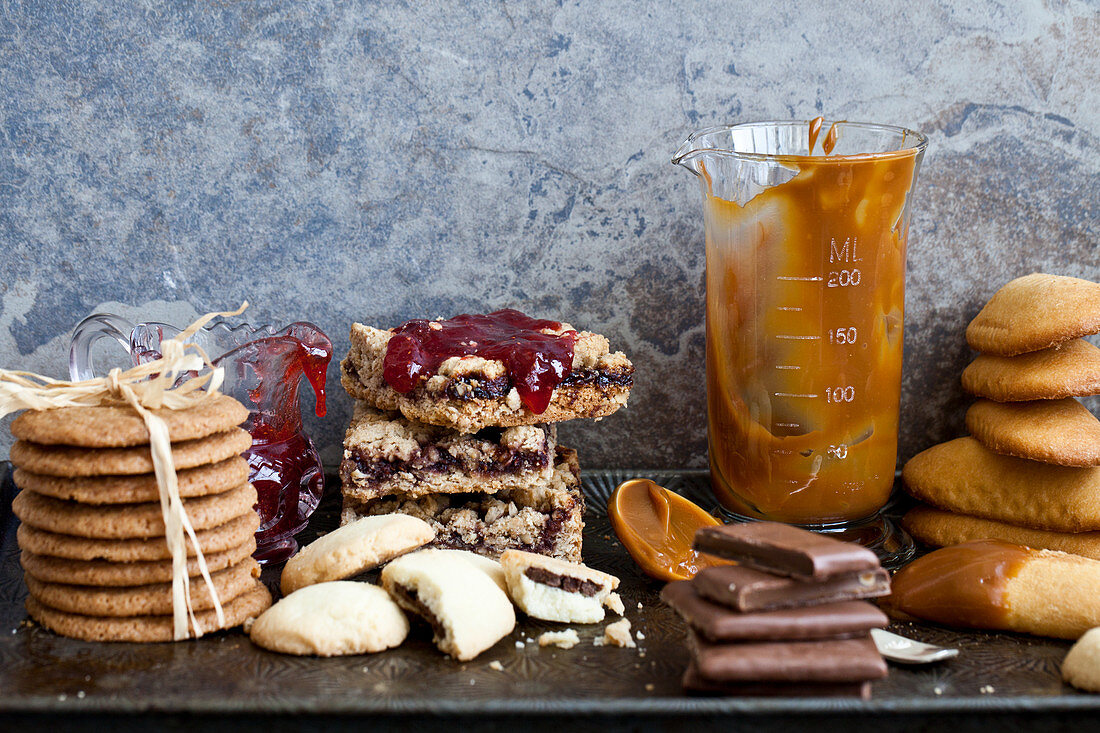 Various cookies stacked on an antique baking sheet, with jam and caramel sauce