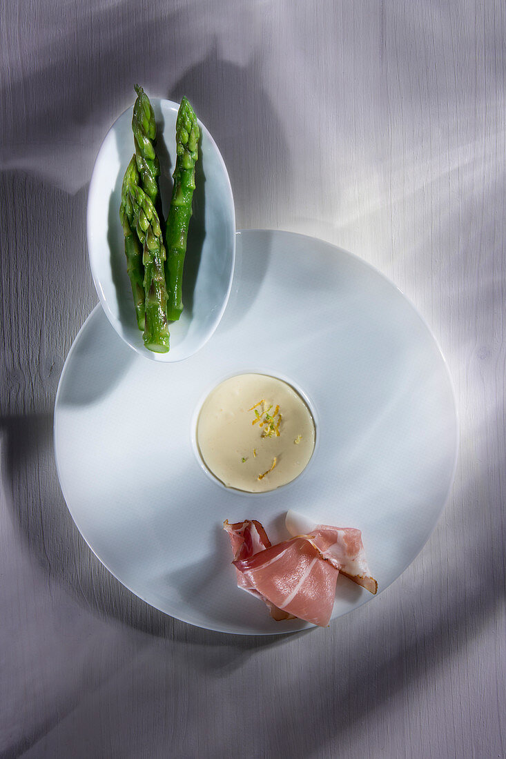 Green asparagus served with ham and sauce Hollandaise