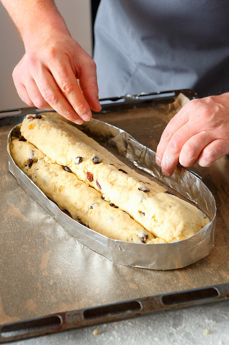 A tin foil edge being made around stollen cake to prevent it from spreading