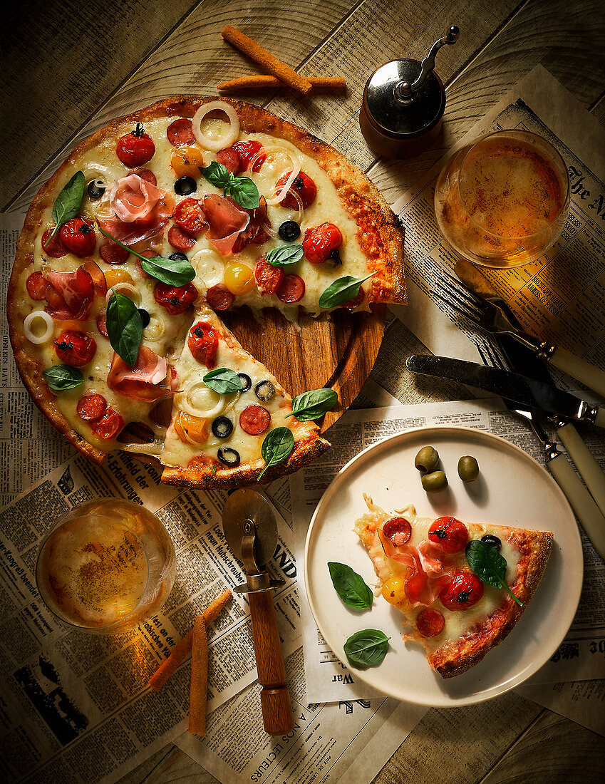 A pizza topped with salami, ham, tomatoes, olives and cheese on a table
