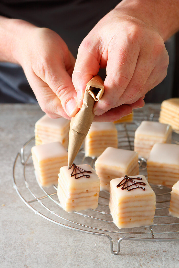Petit fours being decorated with an egg white glaze and chocolate