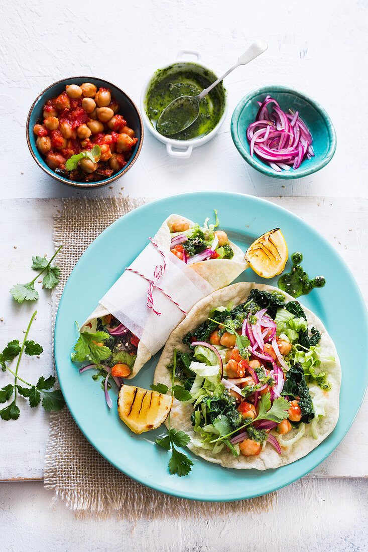 Vegan wraps made with chickpeas, steamed kale, lattuce and pickled red onions, drizzled with kale pesto sauce.