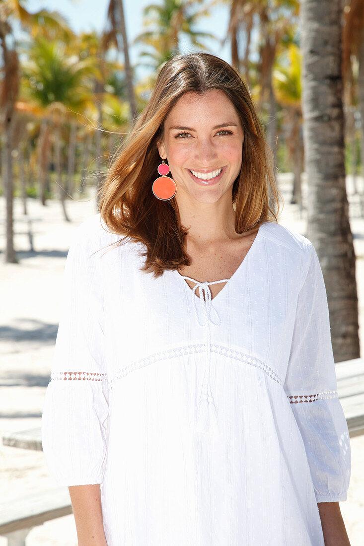 Brünette Frau in weißer Bluse im Freien