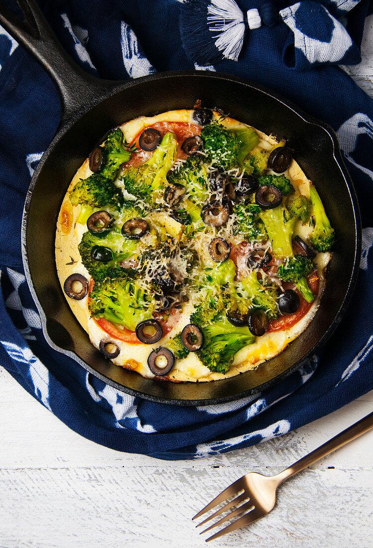 Socca (Kichererbsenfladen) mit Gemüse in Gusseisenpfanne