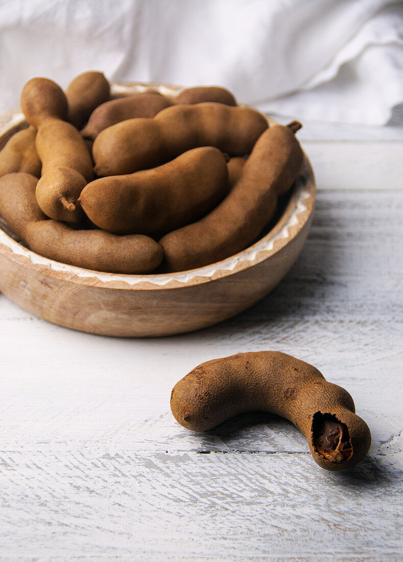 A single tamarind pod and a bowl with tamarind pods