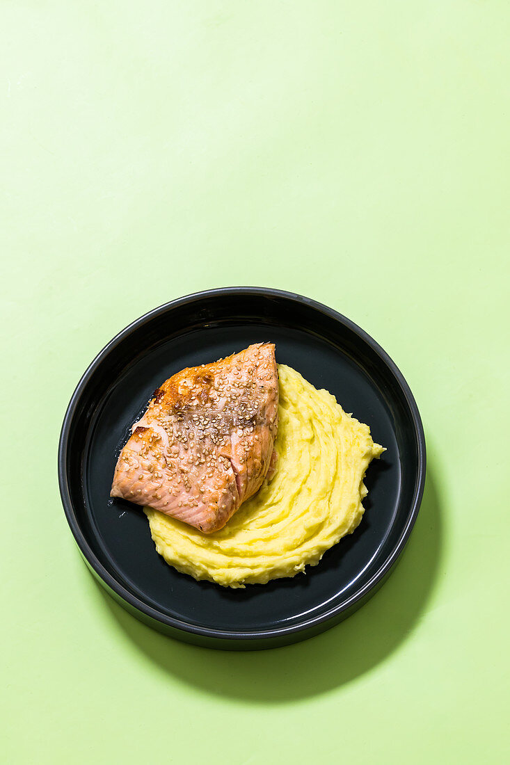 Fried fish on mashed potatoes with wasabi