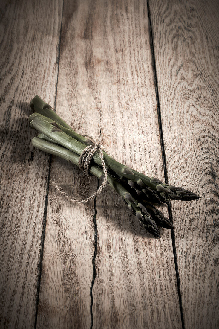 Green asparagus spears tied together on a wooden background
