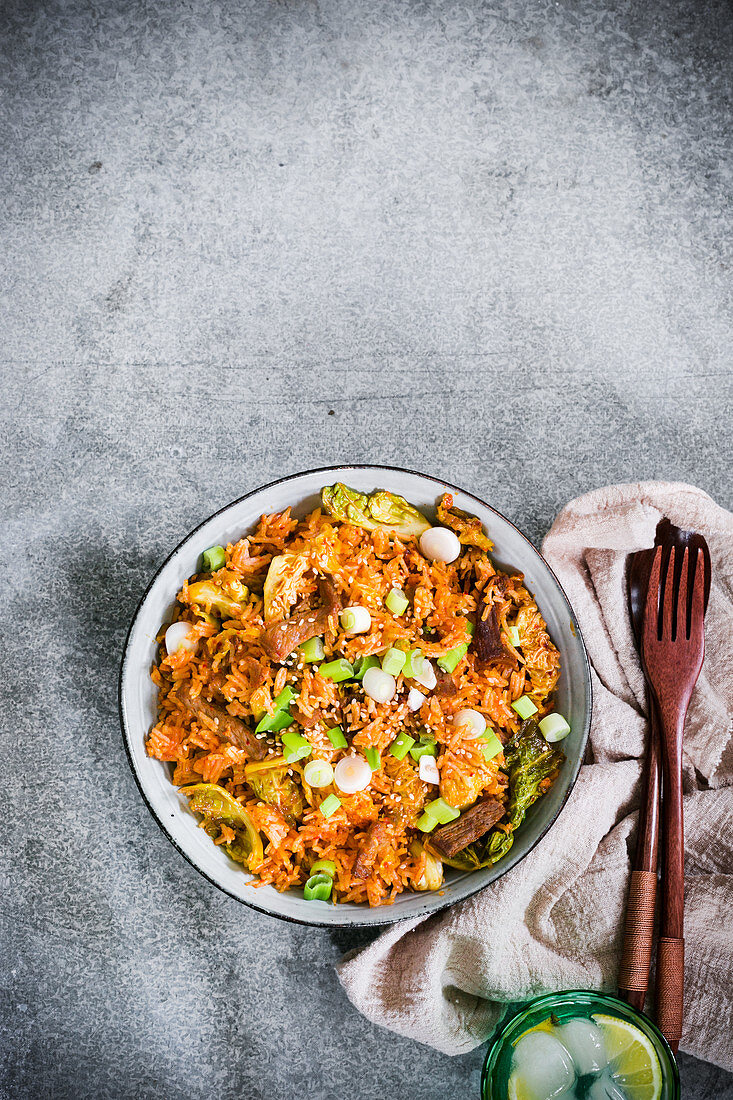 A plate of tradition korean kimchi fried rice with pork and green onions
