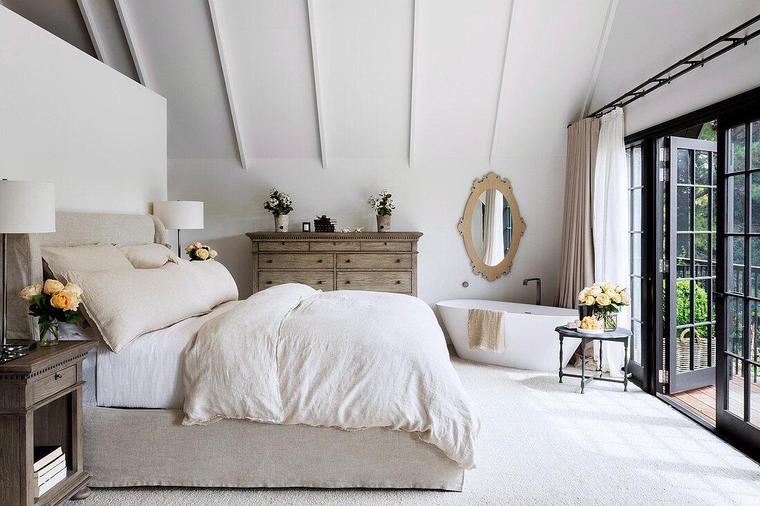 Schlafzimmer mit freistehender Badewanne neben Terrassentür