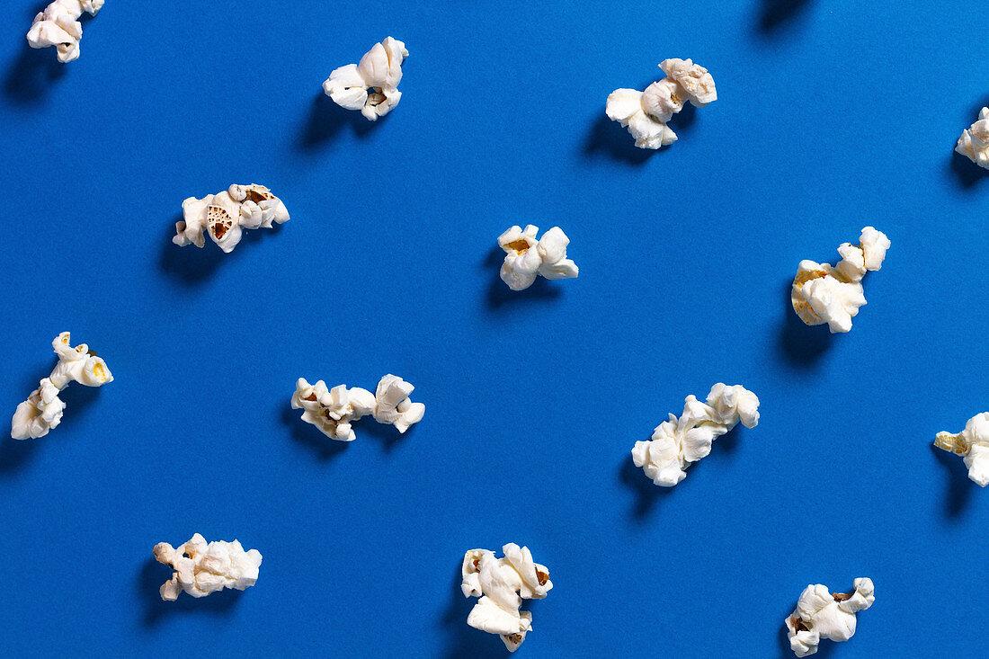 Verstreutes Popcorn auf blauem Untergrund