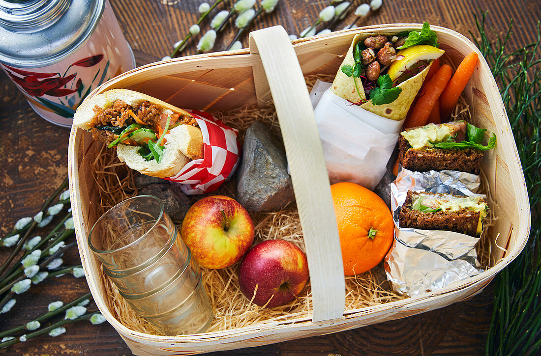 Picknick basket with Vietnameese banh mi-sandwich, ray bread with fillings and a wrap with bean stirring