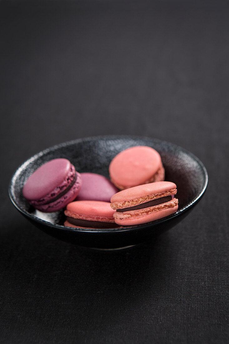 Various pink macarons in a black bowl